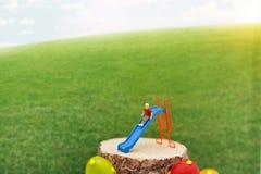 Miniatyrfolk: Barn som spelar glidaren Lycklig familjdag royaltyfri foto