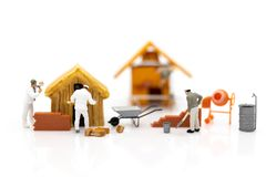 Miniatyrfolk: Byggnadsarbetare som bygger plan, har byggandematerial, sand, tegelsten, mortel Använd bilden för konstruktion royaltyfri foto