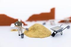 Miniatyrfolk: Byggnadsarbetare som bygger plan, har byggandematerial, sand, tegelsten, mortel Använd bilden för konstruktion arkivbild