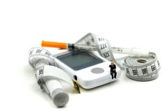 Miniatyrfolk: Doktor och patient med glukosmeterdiabete royaltyfri bild