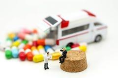 Miniatyrfolk: Doktor och person med paramedicinsk utbildning som in deltar i till patienten Royaltyfria Bilder