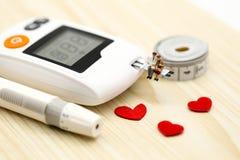 Miniatyrfolk: doktors- och paroldman med glukosmetern arkivbilder