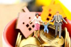 Miniatyrfolk: Familj med det mini- huset med guld- mynt, mortg royaltyfri bild
