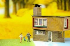 Miniatyrfolk: Familj och barn med huset genom att använda för conc fotografering för bildbyråer
