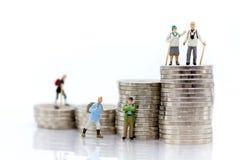 Miniatyrfolk: Gamla människor som överst står av buntmynt Avbilda bruk för bakgrundsavgångplanläggningen, livförsäkringbegrepp royaltyfri fotografi