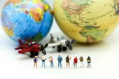 Miniatyrfolk: Handelsresande med världsjordklotet och flygplanet, tra royaltyfri bild