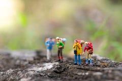 Miniatyrfolk: handelsresanden som går på vägarna, belamras med gräs Van vid lopp till destinationer på loppaffär arkivfoton
