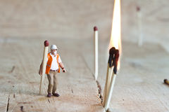 Miniatyrfolk i handling med matchsticks Royaltyfri Foto