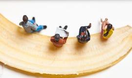 Miniatyrfolk i handling som stting på en banan Royaltyfri Foto