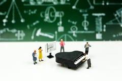 Miniatyrfolk: Lärare och student med pianogrupp av musik arkivfoton