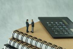 Miniatyrfolk: Litet diagram affärsmanhandshaking och ställning Arkivbild