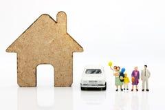 Miniatyrfolk med familjanseende med hus och bilen som är lyckliga arkivbild