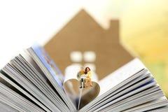 Miniatyrfolk: Par av förälskelse som sitter på boken, utbildning Arkivbild