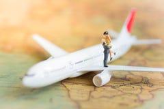 Miniatyrfolk: Par som reser med flygplanet, nivå på en världskarta som används som ett begrepp för affärslopp royaltyfri fotografi