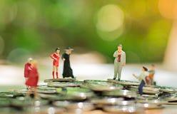 Miniatyrfolk: små diagram affärsmän står överst av mynt runt om tillväxt för begrepp för pilaffärsbusinesspeople som jätte- pekar Royaltyfria Bilder