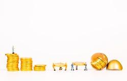 Miniatyrfolk som arbetar med det guld- ägget Royaltyfri Foto