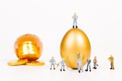 Miniatyrfolk som arbetar med det guld- ägget Royaltyfri Fotografi