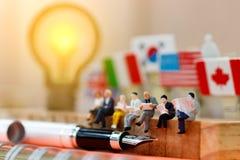 Miniatyrfolk som läser och sitter på trä med lampidé genom att använda som bakgrund, utbildning eller affärsidé royaltyfria bilder