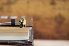 Miniatyrfolk som sitter på hörnet av boken Arkivbild