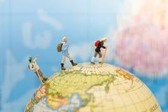 Miniatyrfolk: Ställning för grupphandelsresanderyggsäck och gå på världskarta Avbilda bruk för resa eller affärsturbegrepp royaltyfria bilder