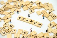 Miniatyrfolkaffärsmän som står med träordet SÖKANDE Finna något svaret till lösningen använda som bakgrund arkivfoton