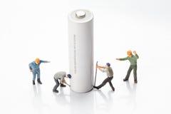 Miniatyrfolket - arbetare som flyttar sig och, återanvänder batterier Arkivfoton