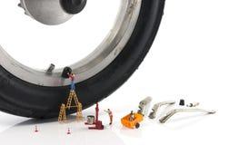 Miniatyrfolket skivar det plana gummihjulet med ventilen Arkivfoto