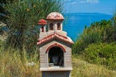 Miniatyrgrekiskt ortodoxt kapell vid havet royaltyfri fotografi