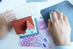 Miniatyrhus på 500 kontanta eurosedlar framme av en affärskvinna som arbetar på en dator Arkivfoton