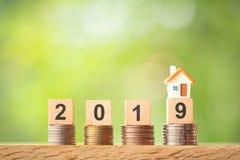 Miniatyrhusmodell på året 2019 på myntbuntar på suddig bakgrund för grönska royaltyfri fotografi