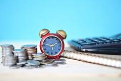 Miniatyrklocka- och myntbunt på skrivbordtabellen Fotografering för Bildbyråer