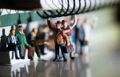 Miniatyrleksak av folk som reser från arbete på ett kollektivtrafikbegrepp royaltyfri foto