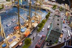 Miniatyrmodell av staden med en skeppsdocka, en segling och leksakbilar Royaltyfria Bilder