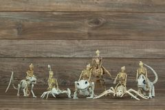 Miniatyrskelett- armé på wood bakgrund arkivbilder