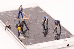 Miniatyrspricka för folkreparationssmartphone arkivfoto
