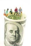 Miniatyrstatyettdiskussion på kanten av 100 dollar banknot Royaltyfri Bild