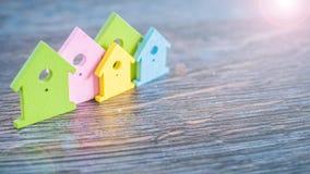 Miniatyrsymbolet av olika färgade hus som blir i grupp i ljus, blossar på mörk träyttersida Arkivfoto