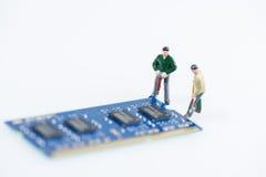 Miniatyrtekniker som arbetar på det datorRAM slutet upp över vit bakgrund Royaltyfri Foto
