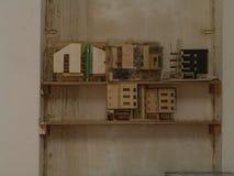 Miniatyrträbyggnader på skärm på en trähylla mot en vägg arkivfoton