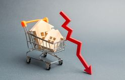 Miniatyrtr?hus och en r?d pil ner Begreppet av low costfastigheten L?gre inteckna r?ntesatser fallande priser arkivbilder