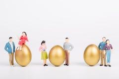 Miniaure-Leute mit Goldei lizenzfreies stockbild