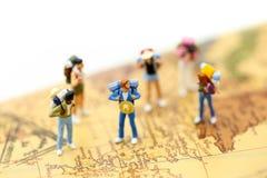 Miniauture-Leute: Reisendrucksack, der auf Weltkarte, Trav steht Stockbild