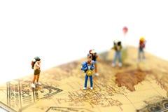 Miniauture-Leute: Reisendrucksack, der auf Weltkarte, Trav steht Lizenzfreies Stockbild