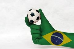 Minibal van voetbal in de geschilderde hand van Brazilië vlag op witte achtergrond stock fotografie