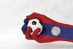 Minibal van voetbal in de geschilderde hand van Laos vlag op witte achtergrond stock fotografie