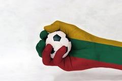Minibal van voetbal in de geschilderde hand van Litouwen vlag op witte achtergrond royalty-vrije stock afbeelding