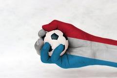 Minibal van voetbal in de geschilderde hand van Luxemburg vlag op witte achtergrond stock afbeeldingen