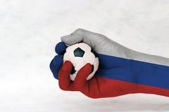 Minibal van voetbal in de geschilderde hand van Rusland vlag op witte achtergrond Concept sport of het spel in handvat of minder  stock afbeeldingen