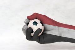 Minibal van voetbal in de geschilderde hand van Yemen vlag op witte achtergrond Concept sport of het spel in handvat of minder be royalty-vrije stock foto's