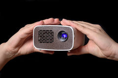 Minibeamer a présenté avec deux mains Photographie stock